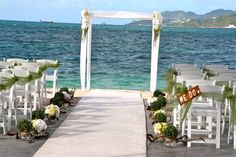 bamboo arch decorated with white and green arrangments, floating woods white and green flowers along the white carpet made by www.fee-des-caraibes.com Face book: Mariages À Saint Martin