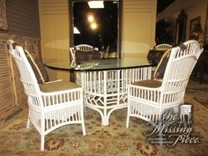 """Glass top table on white rattan base with four chairs. The chairs are upholstered in two complementary patterned fabrics. Nice for a Florida style home! 72""""long x 44""""wide. Arrived: Thursday November 17th, 2016"""
