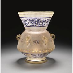 A Gilded & Enamelled Glass Mosque Lamp, made for Abbas Hilmi Pasha (1874-1944), dated A.H. 1328/ A.D.1910  with angled rounded body & wide flaring mouth on a short foot, two wide inscriptive bands around the neck & base in blue enamel with gilded ebellishment, the lower inscription interspersed with three roundels giving the name of 'Abbas Helmi in red enamel, body with floral cartouches between the handles in blue enamel above a cloud band of gilded dots, height 26cm. diam.