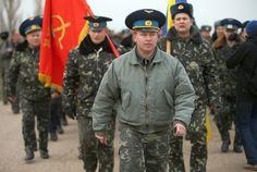 Oberst Juri Mamtschur an der Spitze der unbewaffneten ukrainischen Soldaten einschließlich Flagge der Einheit aus Sowjetzeiten und ukrainischer Flagge.