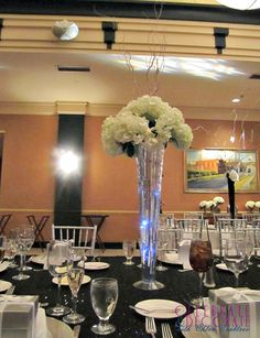 Silver and White centerpieces.  Tall silver vases with lights inside them, white hydrangea and branches.  Perfect for a wedding or a benefit.  #centerpieces #silverandwhitepartydecor #silverblackwhiteparty