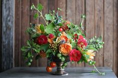 Floret Flower Farm - bronze compote flower arrangement of orange peach garden roses, tomatoes, cranberry viburnum, red ranunculus, nasturtium