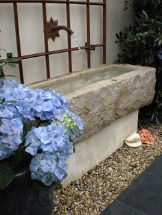 Use the lion head fountain on a 4x4 and cast our own cement trough to act as a separator on one end of flagstone patio