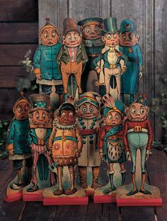 """American Lithographed-Paper-over-Wood Brownies with Original Stands  12"""" (30 cm.) The flat die-cut wooden figures have lithographed-paper cover to depict the various Brownie characters,along with original red wooden slot bases for display that appeared in the various Palmer Cox books. Each marked """"copyrighted 1892 by Palmer Cox""""."""