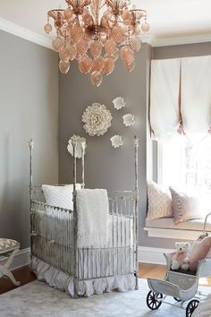 Pink and grey girl's nursery features a pale pink ceiling accented with a pink chandelier, Bello Vetro Glass Chandelier, over gray walls fitted with a built-in window seat accented with pink and gray pillows.