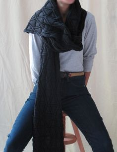 A hand knitted scarf with an embossed diamond pattern.