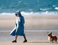 Queen Elizabeth and one of her Corgis taking a stroll on the beach.