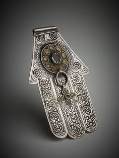Morocco - 1890s. Silver 'Hand of Fatima' or 'khamsa' (meaning 'five') amuletic pendant in the shape of a hand.silver,glass, enamel .