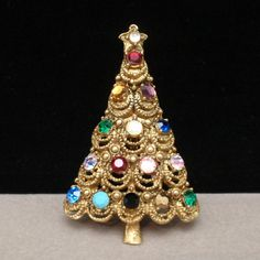 Antique gold tone metal Christmas tree pin with multi-colored rhinestones. The tree has a scalloped edge on the bottom. It closes with a safety clasp. This tree is hallmarked Hollycraft on the reverse