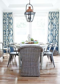 Spring Dining Room - white farmhouse table, big lantern, wicker chairs, tolix chairs, blue ikat window treatments