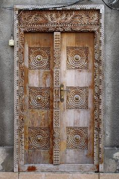 a series of house doors in Zanzibar (particularly in Stone Town), by Turkish photographer CENGİZ AKDUMAN (The greater the wealth and status of the house's owner, the larger and more elaborately carved his front door.