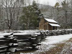 An historic cabin covered in snow at Cades Cove in winter.