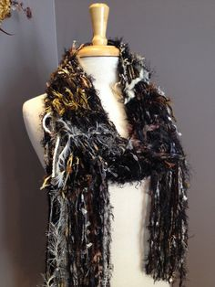 Fringed knit Fashion Scarf - Rare Woods Dumpster Diva Drop-Knit Fringed Scarf in cream, brown, gold, black for women, fashion, scarves, gifts  This piece is a fun, artistic, shaggy way to show your dumpster diva style! Its a collection of over 18 different materials, hand tied and knit together in a drop knit see-through pattern scarf, blended with a luxuriously soft black acrylic fluffy base material. Wear it with diamonds or jeans.. it will add fashion-proof flair to whatever you decide to…