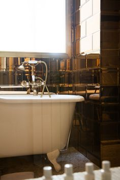 Hollywood Regency Midcentury Hardware: Brown mirrored tiles surrounding bathtub.