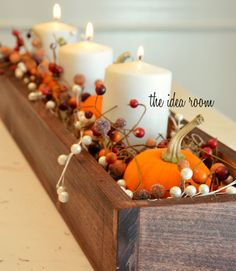 I love this for fall decor before and after our Halloween celebrations. Cushion candles, pumpkins, and berry garlands with Spanish moss to fashion a simple, beautiful centerpiece. Get the tutorial at The Idea Room.   - CountryLiving.com
