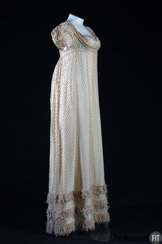 "Evening Dress: ca. 1810, English, silk tricot, embellished with fringe and cord. ""The high waistline and small bust of this dress typify the prevailing style of the first French Empire. The openwork knit fabric reveals much of the wearer's underclothing while also clinging to her figure, daring to highlight the natural female form..."""