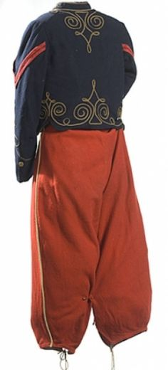 CIVIL WAR-ERA CHILD`S ZOUAVE UNIFORM, blue wool jacket with red edging and gilt piping on sleeves, collar and front with 8 flat brass loop-back buttons and red corporal stripes on each arm, quilted green linen lining with cotton ticking lining sleeves, interior pocket on left. Red wool pants with white piping and drawstring leg closure and mixture of buttons at waist and fly.