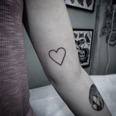 Hand poked heart tattoo on the left inner arm.