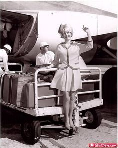 Vintage photo of a stylish air stewardess posing while luggage is being loaded onto the plane. Cute!