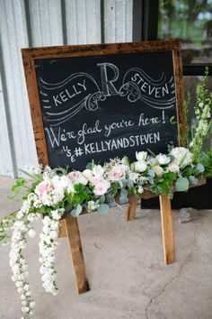 wooden chalkboard welcome wedding sign with loose floral arrangement