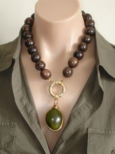 ASHIRA Ebony Wood Necklace with Khaki-Olive Green Tagua Ivory Nut Pendant Wire Wrapped in Brass. $160.00, via Etsy.