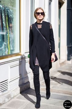 Olivia Palermo wears a paneled black top, tweed shorts, a black vest,  thigh-high boots, and a crossbody bag a1b548095484