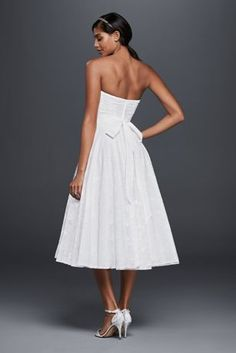 We love to picture this tea-length lace wedding dress at a garden ceremony. The drop waist and higher hemline give the little white dress an undeniably ladylike vibe that's heightened by the 3D flower that blossoms at the waist. David's Bridal Collection Polyester Back zipper; fully lined Dry clean Imported