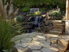 Stone stairs draw the eye up to a second, higher seating area in this multi-level outdoor space.