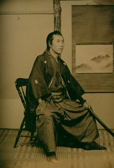 """Photograph by Shimooka Renjo; """"Samurai Uchida""""; Charles Schwartz.    At the end of the samurai era, once fierce warriors had enough time on their hands to sit for portraits. This aristocratic samurai from the late 1800s posed with his katana sword prominently displayed and still in its scabbard with the cords tied."""