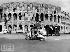 A couple sharing a ride on a Vespa scooter in front of the Colosseum in Rome, 1952