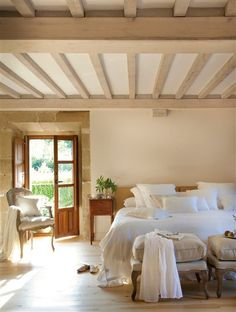 Bright white bed linens and natural, neutral decor are perfect beneath the beams in the ceiling of the master bedroom of a California ranch-style home.