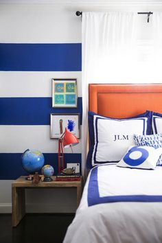 Sally Wheat - Blue and orange boy's room with white and blue horizontal striped walls as well as orange headboard with nailhead trim accented in white and blue monogrammed bedding placed in front of window covered in white curtains next to re-claimed wood bedside table topped with red task lamp and globes.