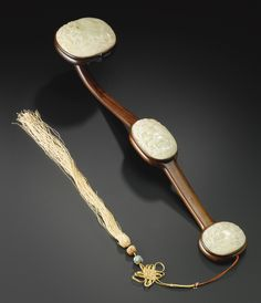 A WHITE JADE-INLAID WOOD RUYI SCEPTER, QING DYNASTY, 18TH / 19TH CENTURY inset with three jade oval plaques carved in shallow relief with auspicious emblems, two deer in a landscape setting with lingzhi on the ruyi head, the mid-section with a crane beneath pine trees, and a peach tree with a further lingzhi on the base, pierced and strung with a silk tassel.