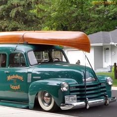 Slammed 1947-53 Chevy Suburban Carryall. Very cool theme with a lodge door logo and the wooden canoe.  #brotherstrucks #chevrolet #chevy #gmc #classic #vintage #classictruck #pickup #truck #3100 #advancedesign #automotive #restoration #whitewalls #camping #canoe