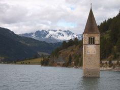 reschensee, italy (lake reschen). The top of a 14th-century church tower from the submerged village is still visible. In winter, when the lake freezes, the tower is reachable by foot