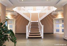 Die STREGER-Treppe in T-Form ist eine stilgerechte Lösung für großzügige Eingangsbereiche. Durch in die Wand eingegossene Auflager wirkt die Treppe freischwebend.