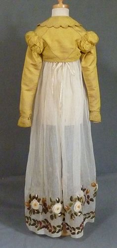 Girl's Spencer early 1820's Deep scalloped collar edged with double row of corded silk satin, bust darts, the back with corded seams, the very long sleeves with shallow puffs silk corded edging and with overlapping silk pleat trim to front and back, the cuffs with a narrow strap and rosette and leaf trim, the edges with four rows of cord quilting, lined with natural colour fine cotton, 30 in or 76 cm bust.