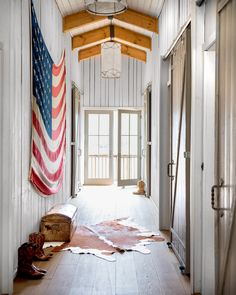 Sliding barn doors with a traditional Z-brace frame complete the bucolic vibe. They're especially striking in the upstairs hallway, where a series of five flanks an antique American flag.