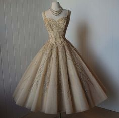 c. 1950s dress of beaded nude tulle with a boned corset bodice and a full circle skirt with 4 layers of tule.