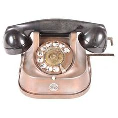 """Vintage brass telephone from 1956. Decorative use only.     Product: TelephoneConstruction Material: BrassColor: Black and brownFeatures:  Initialed """"RTT"""" on front of receiverDimensions: 5.5"""" H x 5"""" W x 9"""" DNote: For decorative purposes only. Due to the vintage nature of this product, some wear and tear is to be expected. Products may show signs of brand marks, scrapes or other blemishes. Cleaning and Care: Wipe with damp cloth"""
