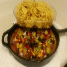 Cheesy ooey gooey bean dip layered with beans, cheese, bacon, two kinds of cheese, jalapenoo, tomatoes, onions and olives served warm from the oven with tortilla chips.