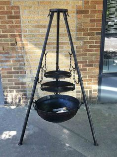 """Rugged Tri-Pod grill from Nomadic Grill is perfect for the cabin, backyard or base camp. Two grill grates (18"""" & 14"""" diameters) hang from chains on the tri pod with a variety of adjustments above the"""