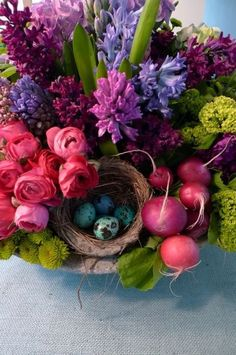 bowl of blue, pink and purple English hyacinth, green Kermit mums, pink rennuculus, radishes (and maybe green hydrangeas or poms) with bird nest and blue eggs