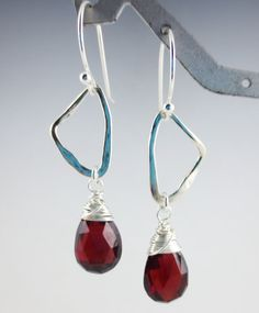 $36.99 Unique earrings feature genuine garnet gemstones suspended from abstract sterling links.