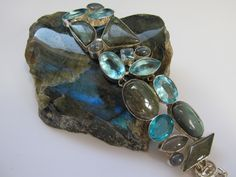 A sophisticated pairing of 9 large and small highly polished cabachon Labradorite gemstones, adorned with 7 faceted London Blue Topaz gemstones, bezel-set in 925-hallmarked sterling silver, with adjus