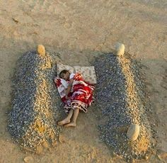 Syrian boy sleeping between his parents.