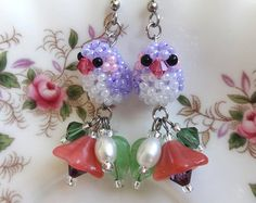 Bright and colourful purple bead bird and flowers earrings for spring or summer outfits. Colourful + Whimsical + Handmade Jewellery by The Glittering Glade