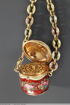 18th century gold and enamel vinaigrette, circa 1785. Antique gold and enamel vinaigrette with polychrome enamel bunches of roses, suspended from two chains joined to a ring with scalloped edge, heightened with gold floral motifs on purple, green and red background. French marks for gold : tête de vanneau (1783-1789) on the vinaigrette and tête de bélier (1819-1838) on the ring.