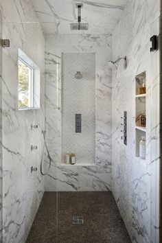 marble walk in shower with a different floor and built in shelves