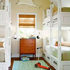 Built-in white bunks and dark wood dresser make a handsome statement in a beach home that consists of ocean-colors.